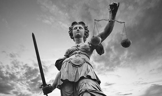 черно бяла снимка на статуята на Темида, която държи меч и везна